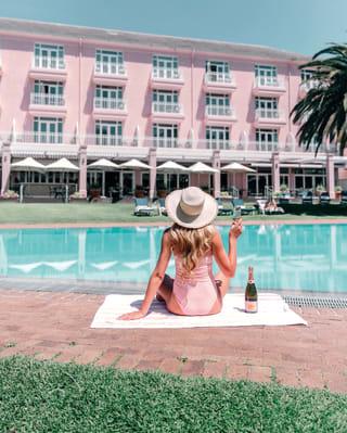 Mulher em um traje de banho rosa bebendo champanhe rosé ao lado da piscina