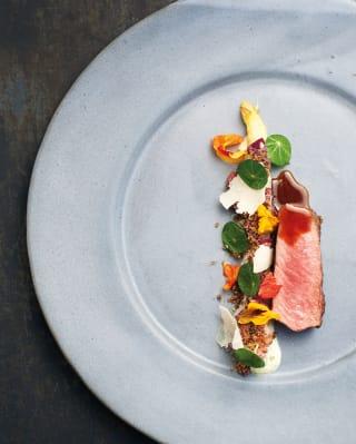 Visão panorâmica de um carpaccio bovino em um prato branco redondo