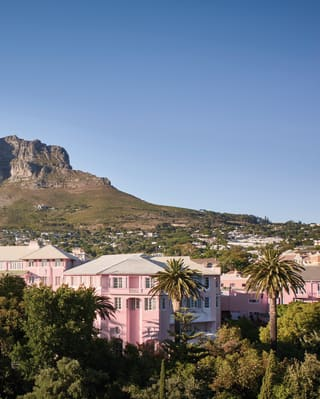 Pink hotel among lush gardens with mountains behind