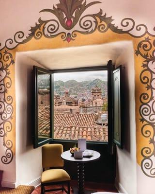 Janela do quarto de hotel aberta com vista do horizonte de Cusco