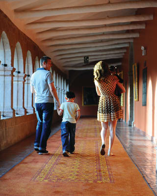 A family of three walking along a cloister with artwork lining the walls