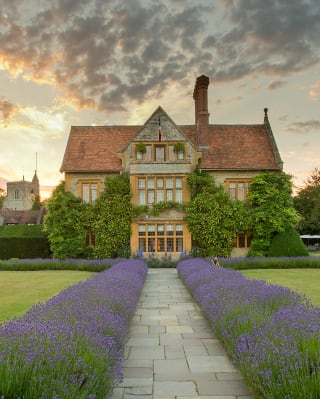 A lavender-lined garden path leading to a Manor House hotel