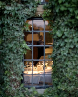 Wine glasses on a table through an ivy surrounded window