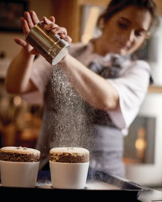Lady in an grey apron using an icing sugar shaker