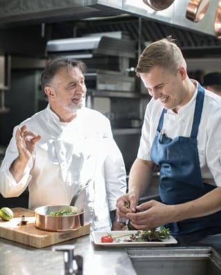 Lo chef Raymond Blanc sorride con un altro chef nella cucina di un hotel