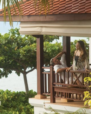 Couple smiling and relaxing on an open air veranda