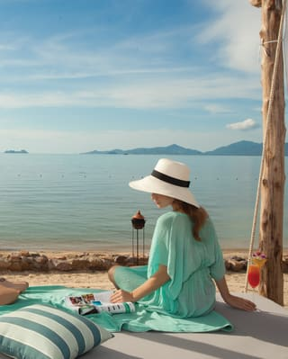 Lady in a sun hat sitting at a lounger on a beach overlooking the Gulf of Thailand