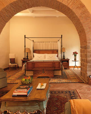 Lounge area with a red-brick colonial style arch leading to a bedroom beyond