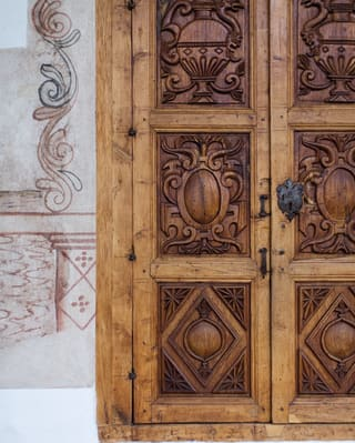 Ornately carved mahogany door with Spanish-colonial style patterning