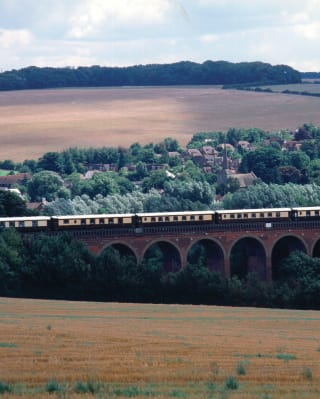 Carriages of the British Pullman crossing a rail viaduct