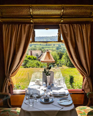 A linen-coated table by a window on a vintage train