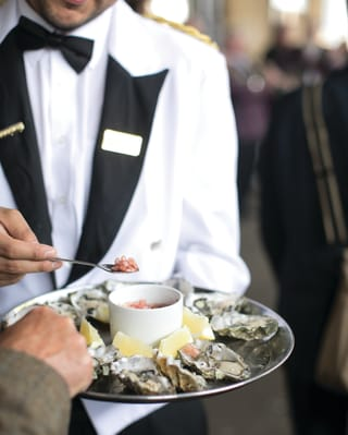 Steward holding a tray of oysters and caviar