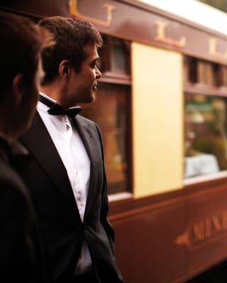 Gentleman in a formal tux looking down the length of a train