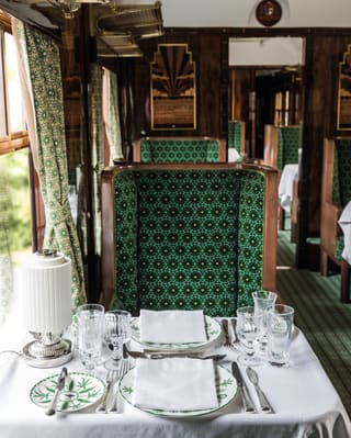 a formal dining table in the carriage designed by Wes Anderson