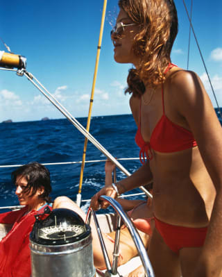 Lady in a red swimsuit steering the wheel of a yacht