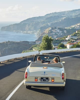 Couple in a vintage car driving along a Madeira highway