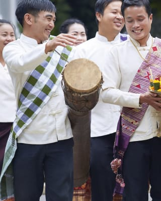 Traditional Laos band playing drums and carrying wedding decorations