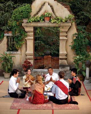 Guests sitting beside a temple joining in a traditional Baci ceremony