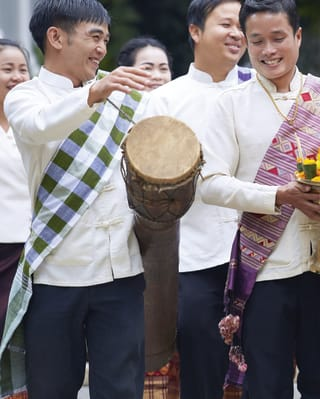 Smiling guests at a traditional Lao wedding ceremony
