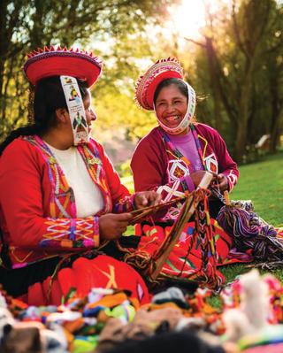 Duas mulheres sorridentes em vestimentas peruanas tradicionais