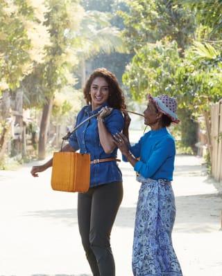 Une villageoise birmane aide une touriste souriante