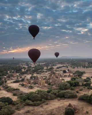 Drei Heißluftballons, die bei Sonnenaufgang über der Ebene von Bangan aufsteigen