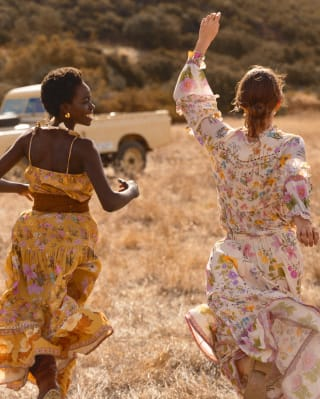 Two ladies running joyfully through grasslands in Botswana