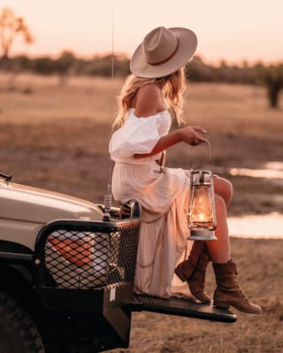 Stylish lady in a flowing white dress holding a lantern and perching on a truck bonnet