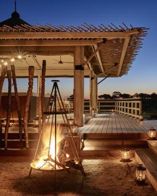 Lit firepit at Savute Elephant Lodge at dusk