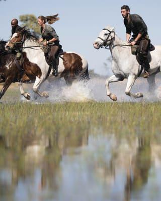 A couple on horseback splashing through flooded grasslands