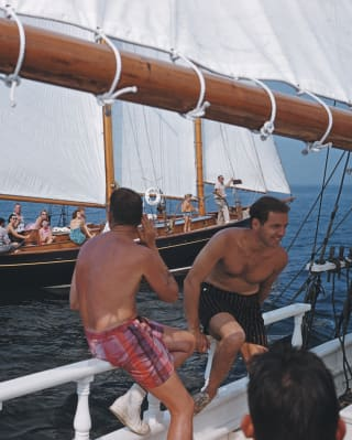 Due uomini che veleggiano in costume su uno yacht lussuoso
