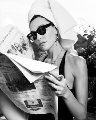 Une femme portant un maillot de bain et des lunettes de soleil lit un journal