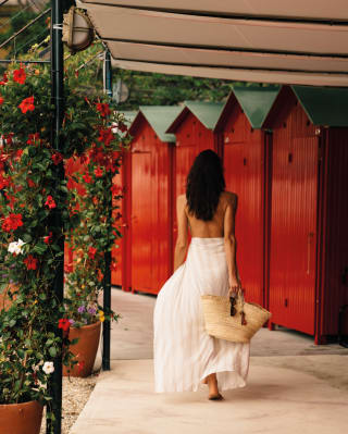 A woman walking in front of beach huts