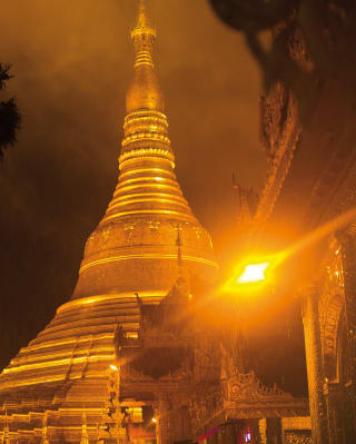The gilded spire of a buddhist temple, the sun sets in the background