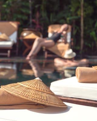 Traditioneller burmesischer Strohhut auf einer Sonnenliege neben einem Outdoor-Pool.