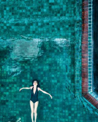 Draufsicht auf eine Dame, die entspannt in einem Outdoor-Pool treibt