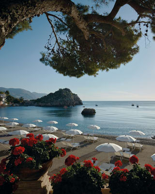 Rows of sun beds and parasols on a beach in Taormina, Italy