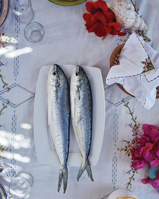 Two fish on a plate in the centre of a table