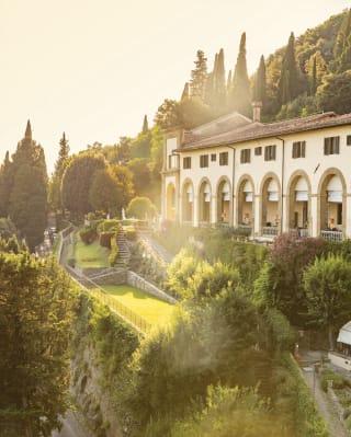 Monastero in collina tra cipressi e giardini rigogliosi