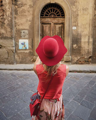 A lady taking a photograph of an Italian street