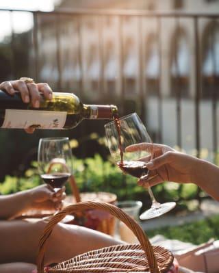 Dettaglio di una mano che versa vino rosso nei bicchieri