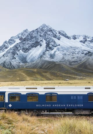 The blue and white carriages of Andean Explorer crossing Peruvian plains