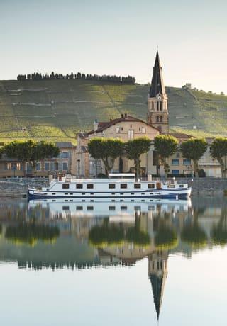 Péniche de luxe passant devant un petit village alsacien, en France