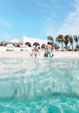 Casal emergindo do Mar do Caribe, com equipamento de snorkel