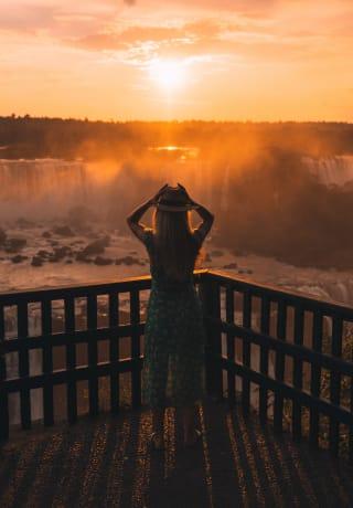 Uma mulher admirando as Cataratas do Iguaçu ao nascer do sol alaranjado