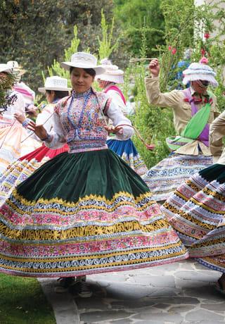 Mulheres em trajes peruanos tradicionais girando e dançando