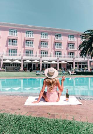 Mulher em um traje de banho rosa bebendo champanhe rosé perto da piscina