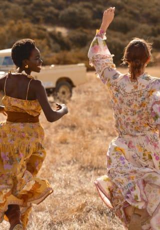 Duas mulheres correndo alegremente pelas savanas