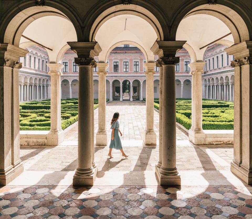 Une femme traverse la cour d'un bâtiment vénitien historique